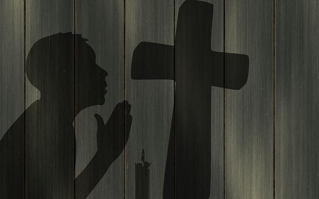 Sombra de menino ajoelhado na cruz